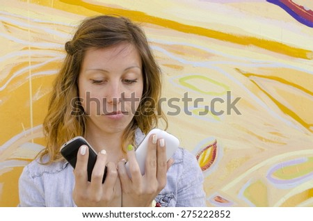 Brunette looking at two mobile phones - stock photo