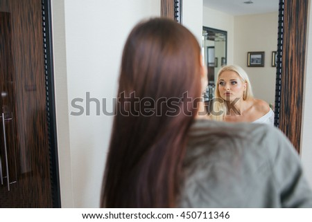Brunette lookst in a mirror where she sees a pretty blonde - stock photo
