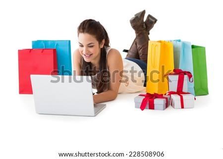 Brunette lying and using her laptop near shopping bags and gifts on white background - stock photo