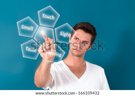 Brunette man Pressing Virtual Button with a blue background - stock photo