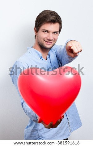 Brunette man wearing a blue shirt and holding a red heart balloon and pointing with finger