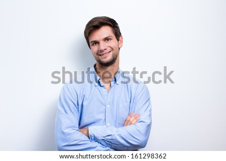 Brunette man with one arm folded wearing a blue shirt - stock photo