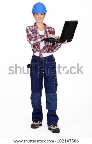 Brunette manual worker holding laptop - stock photo
