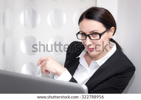 Brunette mature business woman working in a office is giving a over the glasses look in front of the laptop - stock photo