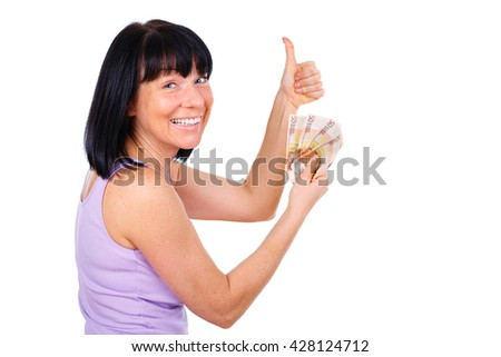 Brunette mature woman with surprised sight and white smiled, holding cash euro money banknotes in hand and show thumb up, isolated on white background, Positive human emotion, facial expression - stock photo