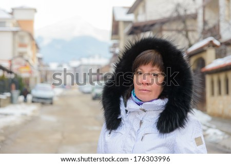 Brunette middle-aged woman in a stylish white jacket with a fur collar