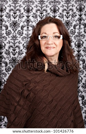 Brunette middle aged woman weather white framed glasses and feather hair extensions and accessories. - stock photo