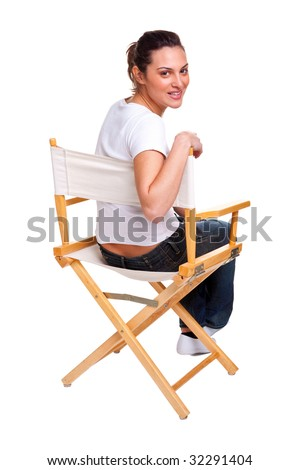 Brunette model sat in a directors chair looking back over her shoulder, isolated on white. Add your own text to the back of the chair. - stock photo