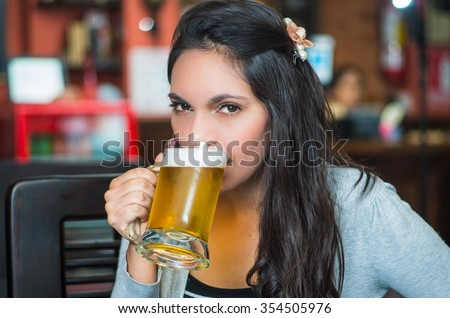 Brunette model sitting by restaurant table drinking from glass of beer and posing with positive attitude smiling. - stock photo