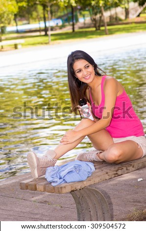 Brunette model wearing pink top and white shorts relaxing in park environment, sitting on bench next to lake using insect repellent spray smiling at camera.