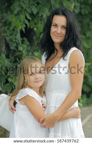 Brunette mother and blond daughter in white - stock photo