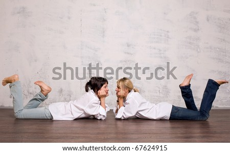 Brunette mother ang her blond daughter lying on the floor and looking to each other - stock photo