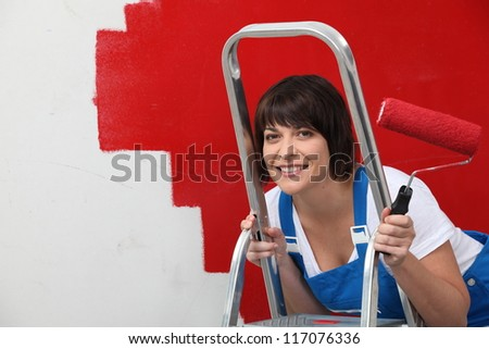 Brunette painting wall in red - stock photo