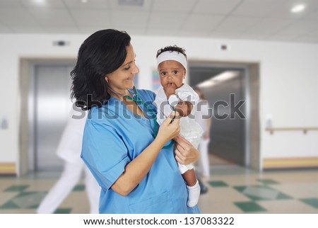 Brunette pediatrician at the hospital with a beautiful baby - stock photo