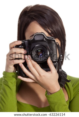 Brunette photographer holding slr camera up to her eye and aiming at camera. - stock photo