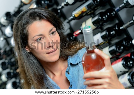Brunette picking out a bottle of wine - stock photo