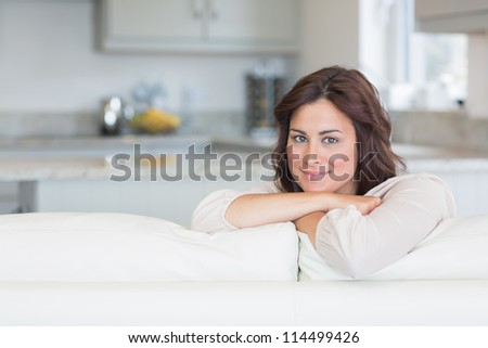 Brunette relaxing on the sofa and smiling - stock photo
