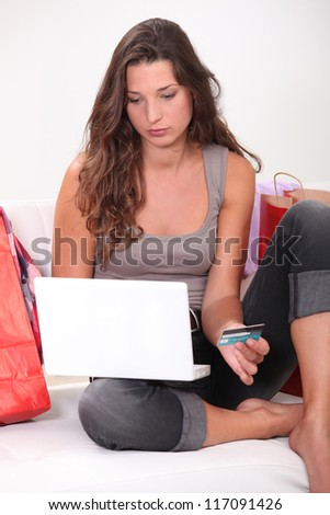 Brunette sat at home shopping on-line - stock photo