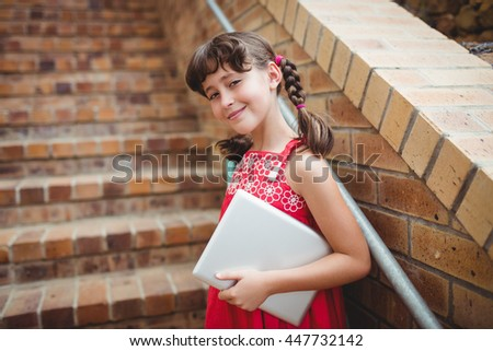 Brunette schoolgirl holding a digital tablet in the stairs - stock photo