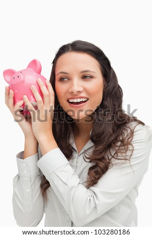 Brunette shaking a piggy bank against white background - stock photo