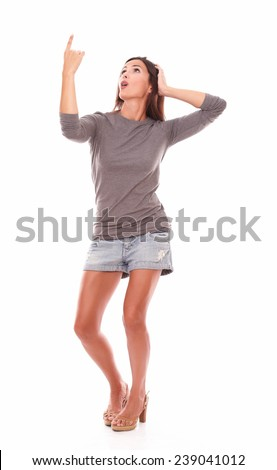 Brunette standing full length while pointing up wearing shorts jeans in white background - copyspace - stock photo