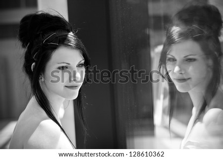 Brunette staring out the window and her portrait is reflected in the glass - stock photo