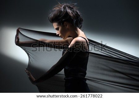 Brunette stretches stretch mesh fabric in front of you - stock photo