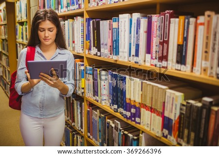 Brunette student using her tablet next to bookshelves in library - stock photo