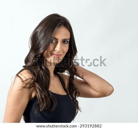 Brunette tanned beauty with hand touching her wavy long hair. Portrait over gray studio background. - stock photo