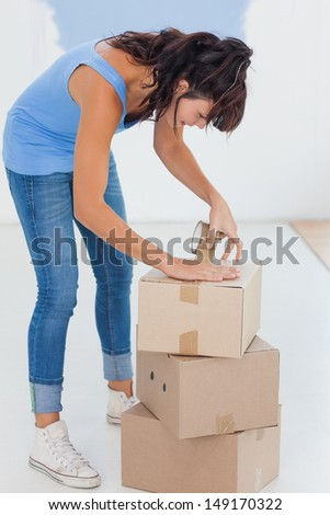 Brunette taping up moving boxes in an empty room - stock photo