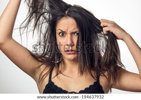 Brunette teenager girl with anger expression pulling her messy hair - stock photo