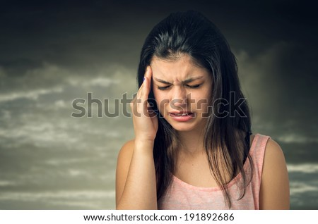 Brunette teenager girl with painful expression and hand on her head
