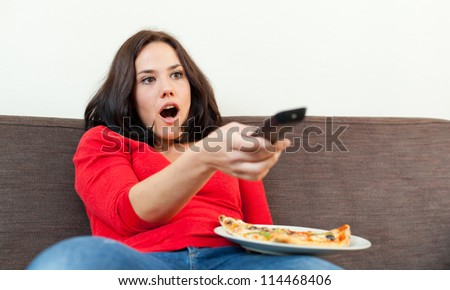 Brunette with a pizza, watching tv and looking amazed - stock photo