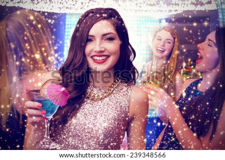 Brunette with cocktail against gold and red lights - stock photo
