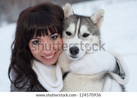 Brunette with dog in winter forest