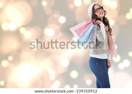 Brunette with glasses holding shopping bags against blurred lights - stock photo