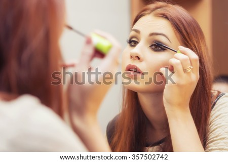 Brunette woman applying make up (paint her eyelashes) for a evening date in front of a mirror. Focus on her reflection - stock photo