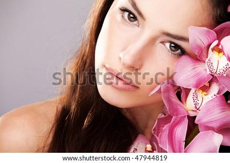 brunette woman beauty portrait with orchid - stock photo