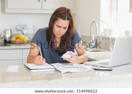 Brunette woman calculating bills in the kitchen