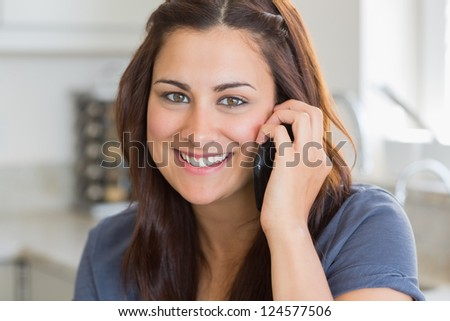 Brunette woman calling in the kitchen and smiling - stock photo