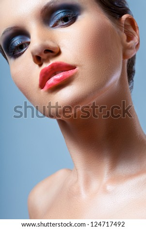 brunette  woman face closeup portrait with smoky eyes makeup over blue background - stock photo