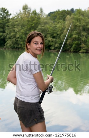 Brunette Woman Fishing at a lake with green water - stock photo