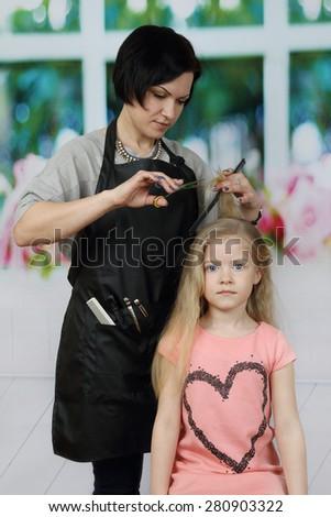 Brunette woman hairdresser cuts little blonde girl long hair - stock photo