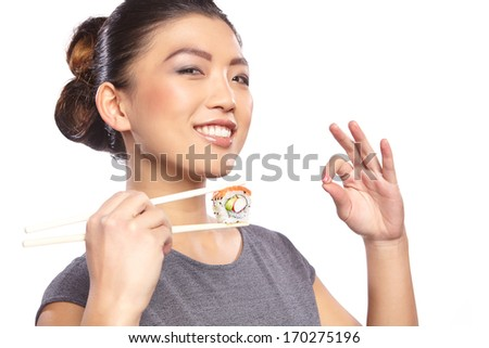 Brunette woman holding sushi with a chopsticks, isolated on white
