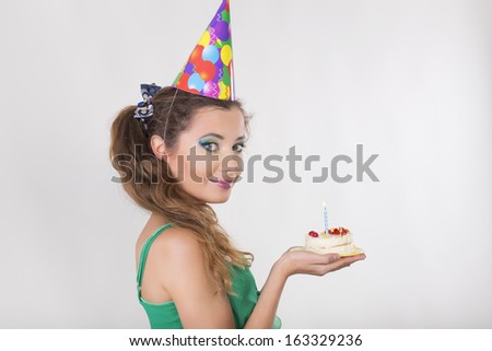 Brunette Woman in a Birthday Cap Holding a Cake and Smile