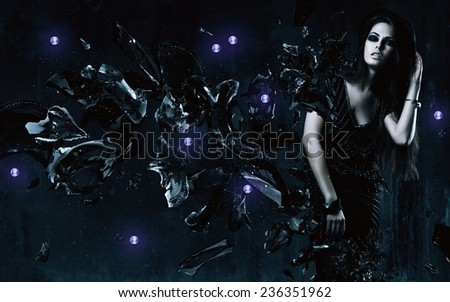brunette woman in black dress and broken glass in dark room - stock photo