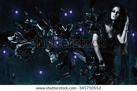 brunette woman in black dress and broken glass in dark room - stock photo