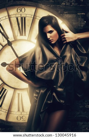 brunette woman in cape at clock - stock photo