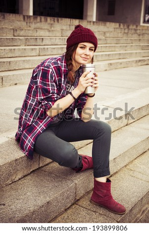 Brunette woman in hipster outfit sitting on steps on the street. Toned image