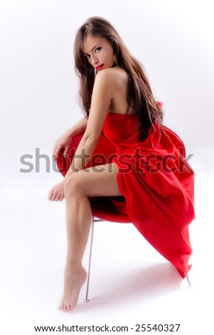 brunette woman in red dress sitting on a red chair